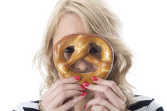 Speelse Jonge Vrouw met Ontbijtpretzel over Gezichtsogen die door piepen Royalty-vrije Stock Afbeelding