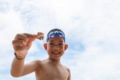Speelse jongen en van de Kluizenaar krab op het strand. royalty-vrije stock foto's