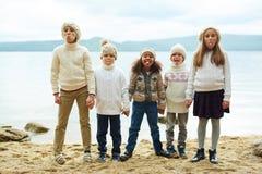 Speelse Kinderen die door Meer stellen Stock Foto