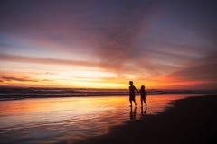 Speelse kinderen op strand in zonsondergangtijd Royalty-vrije Stock Foto's