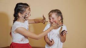 Speelse meisjes die elkaar met verven kleuren stock video