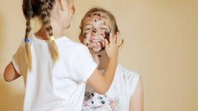 Speelse meisjes die elkaar met verven kleuren stock fotografie