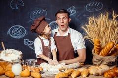 Speelse mens met dochter die brood maken Stock Afbeelding