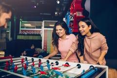 Speelse opgewekte jonge vrouwen die lijstvoetbal met kerel in ruimte spelen Modelleert loook bij spel en controleren het stock afbeeldingen