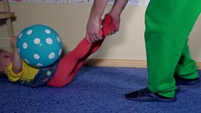Speelse papa die zijn grappige dochter trekken door benen door tapijt op vloer stock footage