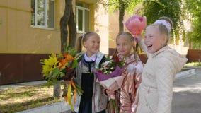 Speelse schoolmeisjes met boeketten die en zich dichtbij school lachen bevinden stock videobeelden