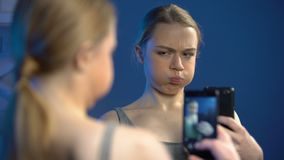 Speelse tiener die gezichten maken, die selfie door smartphonevoorzijde nemen van spiegel stock video