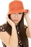 Speelse uitdrukking op tienerjarengezicht die leuke oranje hoed dragen Stock Foto