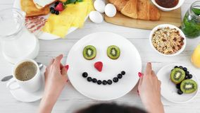 Speelse vrouw die pret hebben die het glimlachen gezicht op plaat maken die vers fruit en bessen hoogste mening gebruiken stock footage