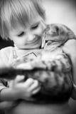 Speelt een meisje en met een kat Stock Afbeeldingen