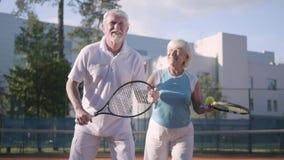 Speeltennis van het portret het gelukkige volwassen paar op een zonnige dag Een oude man en een rijpe vrouw genieten van het spel stock video