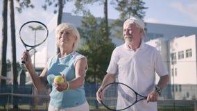 Speeltennis van het portret het gelukkige volwassen paar op een zonnige dag Een oude man en een rijpe vrouw genieten van het spel stock videobeelden