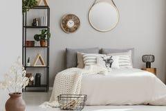 Spegel och träklocka på väggen av det eleganta sovrummet med beige sängkläder och den vita varma filten, verkligt foto royaltyfri foto