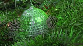 Spegelboll för nytt år mot bakgrunden av dekorerat med en girland av en julgran arkivfilmer