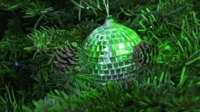 Spegelboll för nytt år mot bakgrunden av dekorerat med en girland av en julgran stock video