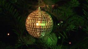 Spegelboll för nytt år mot bakgrunden av dekorerat med en girland av en julgran lager videofilmer