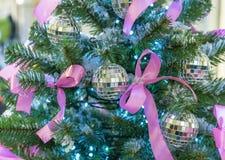 Spegelbollar med rosa pilbågar på julgranen royaltyfria bilder