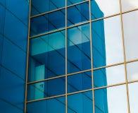Spegelförsedda fönster av fasaden av en kontorsbyggnad med blåa paneler och gula fönsterramar med en förvriden reflexion av royaltyfria bilder