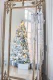 Spegeln reflekterar den dekorerade julgranen, under trädlögngåvorna Royaltyfri Fotografi