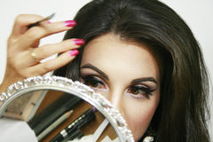 Spegeln reflekterar skönhetsmedlet, och makeupmaterial, den härliga flickan gör hennes makeup, handrörelse, rosa ögonskugga och t Royaltyfria Bilder