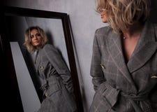 Spegelreflexion av den blonda kvinnabenägenheten mot en vägg royaltyfri fotografi