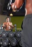 Spegelreflexion av två män som övar i idrottshall Royaltyfri Foto