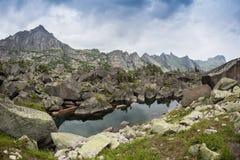 Spegelreflexioner i sjöharmoni i de höga bergen av Ergaki, Ryssland Arkivfoton