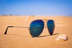 Spegelsolglasögon på stranden, skalet och det stormiga havet reflekteras i exponeringsglasen royaltyfria foton