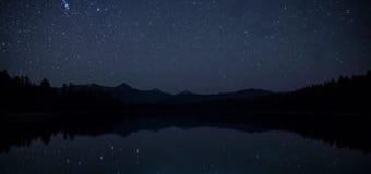 Spegelyttersida hisnande landskap för sjö med bergskedja på natten med himmel med myriader av ljusa stjärnor royaltyfria bilder
