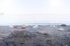 Speicherbereinigung auf dem Strand Plastik und Pakete zerstreut auf den Strand Ein Mann sammelt Plastik ?kologieschutzkonzept stockbild