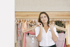 Speichern Sie Assistenten-arbeitende und hängende Kleidung im Speicher stockfoto