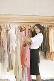 Speichern Sie Assistenten-arbeitende und hängende Kleidung im Speicher lizenzfreie stockfotografie