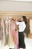 Speichern Sie Assistenten-arbeitende und hängende Kleidung im Speicher lizenzfreies stockfoto