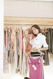 Speichern Sie Assistenten-arbeitende und hängende Kleidung im Speicher lizenzfreies stockbild