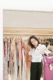 Speichern Sie Assistenten-arbeitende und hängende Kleidung im Speicher stockbilder