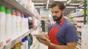 Speichern Sie die Aufsichtskraft mit Tabletten-PC in der Hand die Qualität des Produktes überprüfend im supermarke stock video