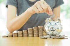 Speichernde geld-junge Frau, die eine Münze in einen Geldkasten setzt Stockfotos