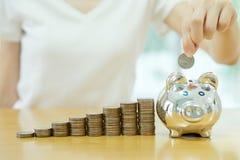 Speichernde geld-junge Frau, die eine Münze in einen Geldkasten setzt Lizenzfreie Stockbilder