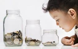 Speicherndes Konzept-junges kleines Mädchen, das Münzen in der Flasche betrachtet stockfotografie