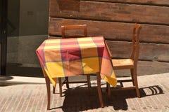 Speisen im Freien im Sommer mit Tabelle und Stühlen Lizenzfreie Stockfotografie