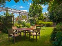 Speisetisch eingestellt in üppigen Garten Lizenzfreie Stockfotos