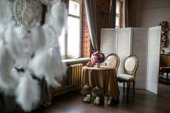 Speisetisch mit klassischen Stühlen, einem Schirm, Frucht, einem Vase Blumen, Kerzen und Traumfängern im Dachbodenraum, Seitenans stockbild