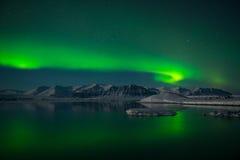 Spektakulär auroral skärm över islagun Jokulsarlon, Island Arkivfoto