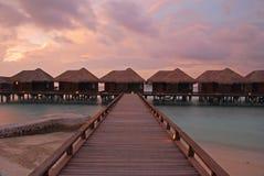 Spektakulär skymning i den tropiska ön förband med trägångbanan Arkivbild