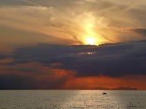 Spektakulär solnedgång med röd himmel och moln över havet av Menorca i Spanien med konturn av ett fartyg på den ljusa reflexionen arkivbild