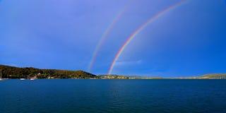 Spektakulärt livligt dubbelt regnbågefoto i blå himmel Arkivfoto