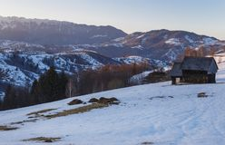 Spektakulärt vinterlandskap Vintersolnedgång, trächalet för gammalt lantligt berg och snöig kullar nära Brasov, Transylvania arkivfoto