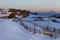 Spektakulärt vinterlandskap Vintersolnedgång, trächalet för gammalt lantligt berg och snöig kullar nära Brasov, Transylvania royaltyfria foton