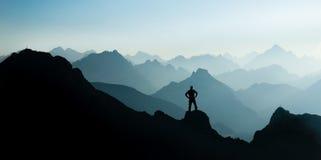 Spektakularne pasmo górskie sylwetki Mężczyzna dojechania szczyt cieszy się wolność zdjęcie royalty free