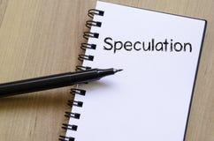 Spekulation skriver på anteckningsboken arkivbild